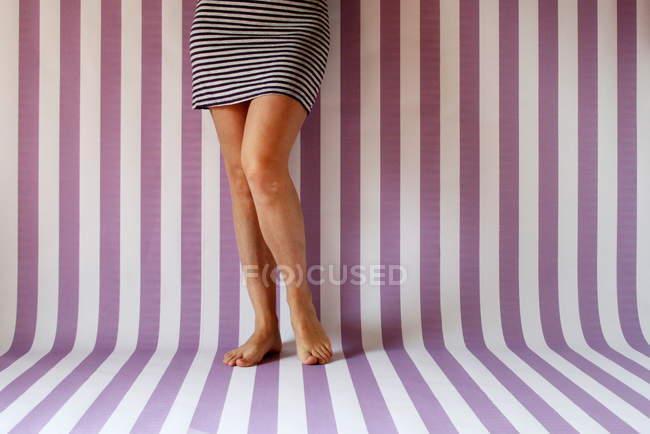 Кадроване зображення жінка ноги тлі смугастий — стокове фото