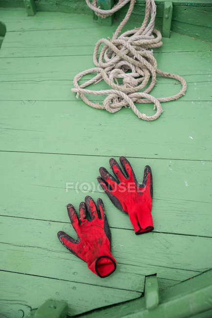 Elevated view of red gloves and rope on a fishing boat — Stock Photo
