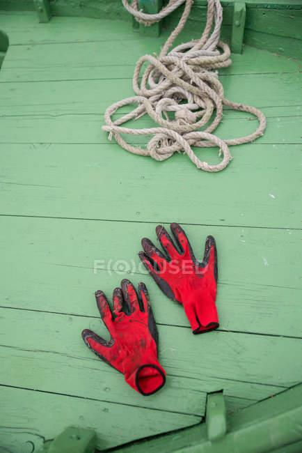 Повышенные вид красных перчатках и веревки на рыбацкой лодке — стоковое фото