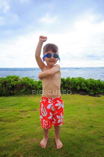 Garçon portant des maillots de bain et des lunettes debout à la prairie avec la mer sur le fond — Photo de stock