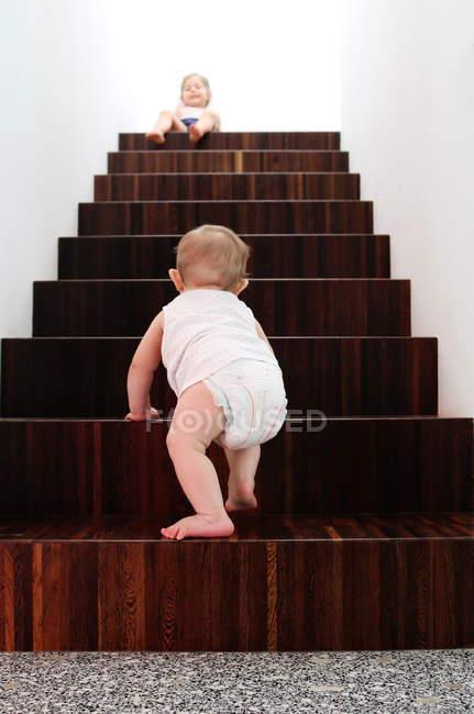 Rückansicht eines kleinen Jungen, der auf Holztreppen klettert, Schwester sitzt oben — Stockfoto