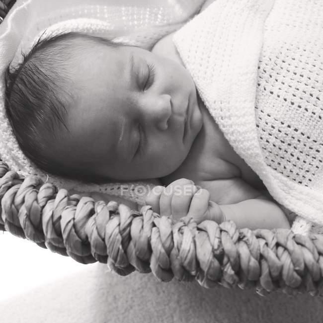 Bambino ragazza dormire in cestino sotto coperta — Foto stock