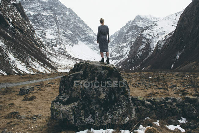Rear view of woman standing on rock between mountains, North Ossetia, Russia — Stock Photo