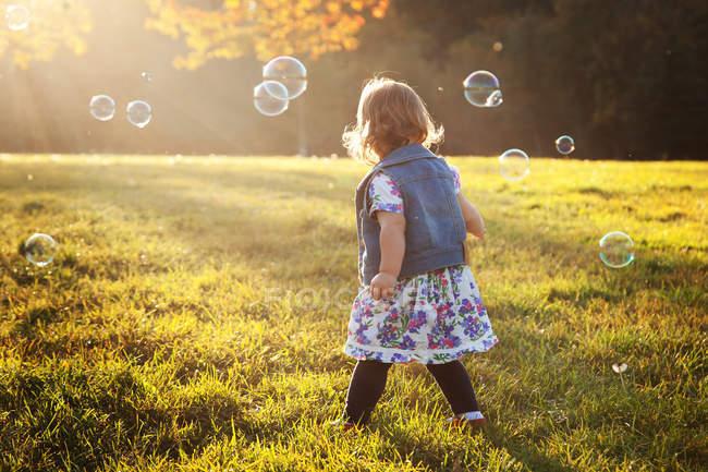 Menina cercada por bolhas de sabão no parque — Fotografia de Stock