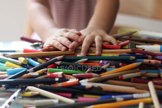 Cerrar la imagen de las manos de los niños con un montón de lápices de colores — Stock Photo