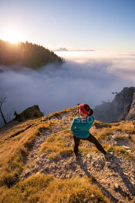 Woman standing on mountain looking at view above clouds, Salzburg, Austria — Stock Photo