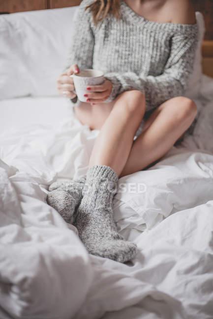 Обрезанный образ привлекательной женщины с красивой кожей в свитере и носки, сидя на кровати с чашкой кофе — стоковое фото