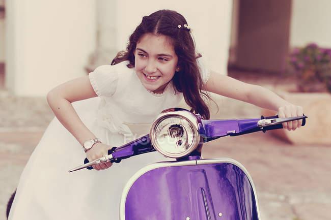 Першого причастя плаття гра на скутері дівчина — стокове фото