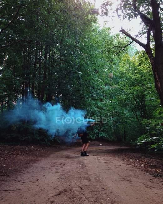 Homme marchant dans la forêt avec une bombe à fumée — Photo de stock