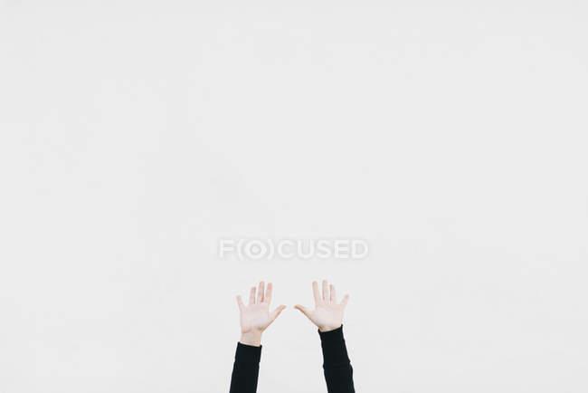 Обрезанное изображение двух рук, прижатых к белой стене — стоковое фото