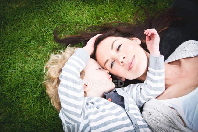 Figlio sdraiato con le braccia intorno al volto della madre — Foto stock