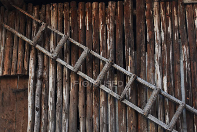 Wooden ladder hanging on wall, full frame — Stock Photo