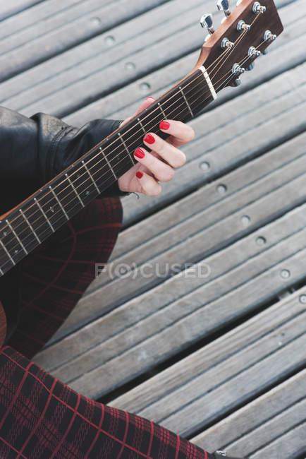 Abgeschnittenes Bild eines Mädchens mit roten Nägeln, das Gitarre spielt — Stockfoto