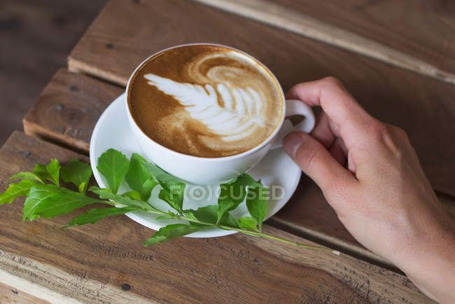 Cropped image of  woman holding cup of cappuccino — Stock Photo