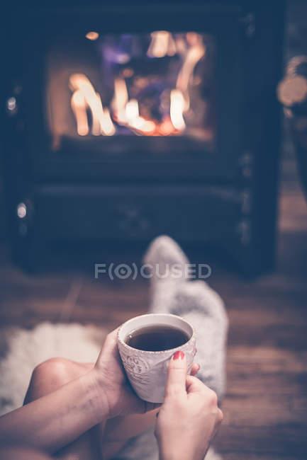 Imagen recortada de la mujer en calcetines sosteniendo la taza de café frente a la chimenea en casa - foto de stock