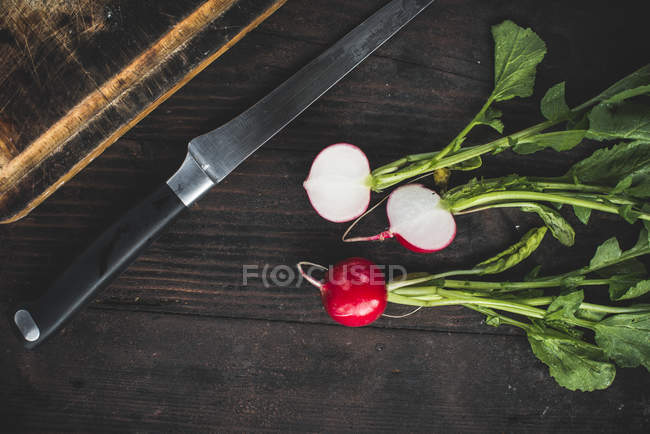 Radishes with a knife and chopping board on a wooden table, top view — Stock Photo