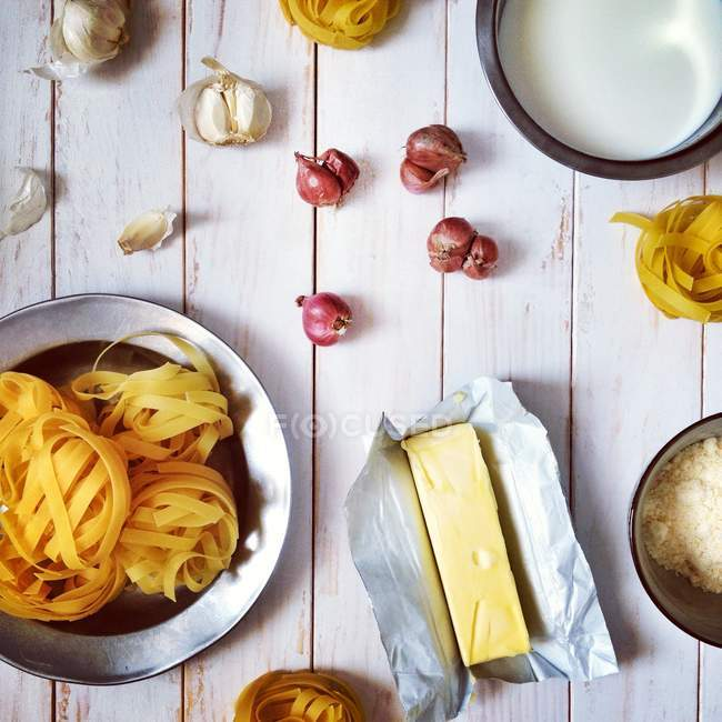 Top view of ingredients for fettuccine alfredo dish over wooden background — Stock Photo
