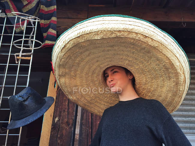 Girl wearing a giant sombrero standing at market, Mexico — Stock Photo