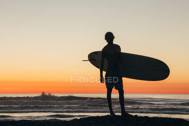 Silhouette of Man standing on beach at sunset holding surfboard — Stock Photo