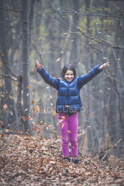 Девушка бросает осенние листья в воздух в лесу — стоковое фото