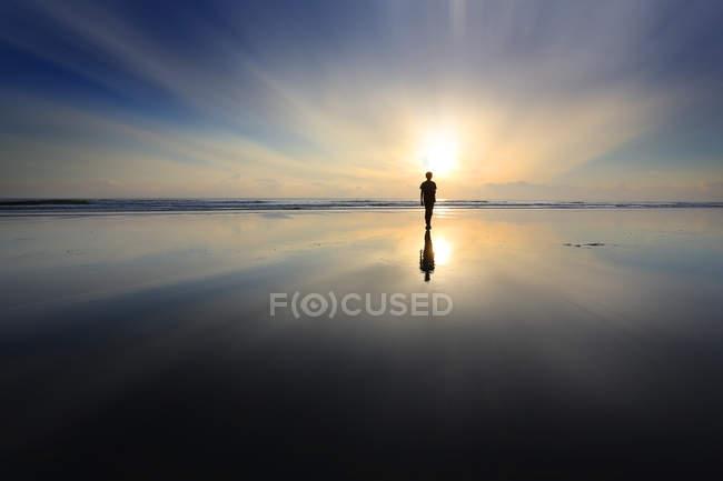 Silueta de niño caminando en la playa al atardecer - foto de stock