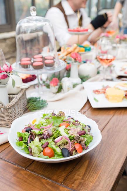 Тарелка салата на столе с кексами, люди на размытом фоне — стоковое фото