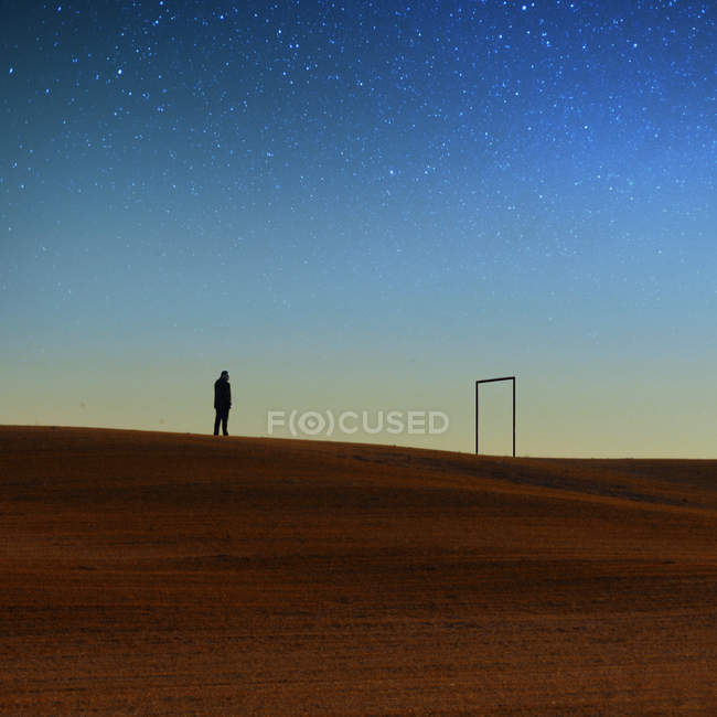 Silhouette of man standing on hill against night sky — Stock Photo