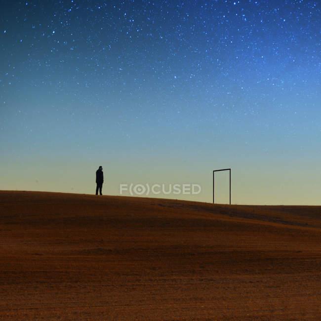 Silhouette de l'homme debout sur la colline contre le ciel nocturne — Photo de stock