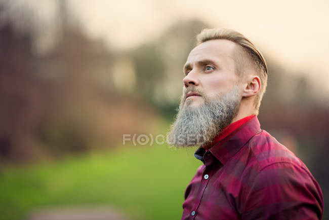 Portrait of funky hipster man with a beard standing outdoors — Stock Photo