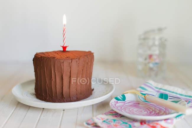 Cioccolato torta di compleanno con la candela sulla piastra sopra fondo di legno — Foto stock