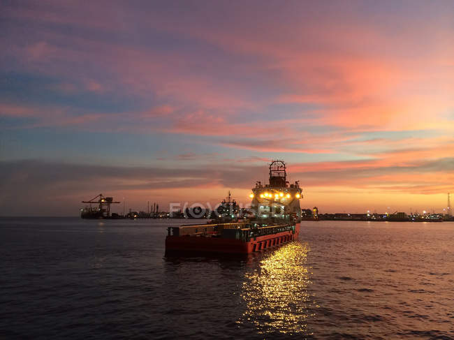 Illuminated oil rig support vessel arriving at port harbor at dusk — Stock Photo