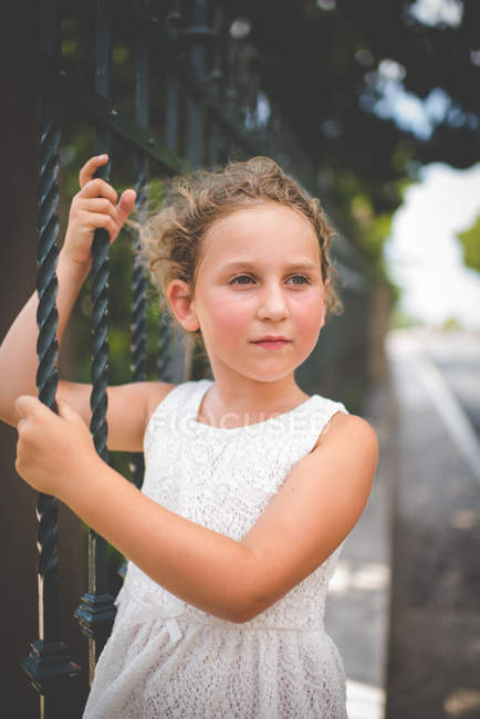 Thoughtful girl hanging from metal railings outdoors — Stock Photo