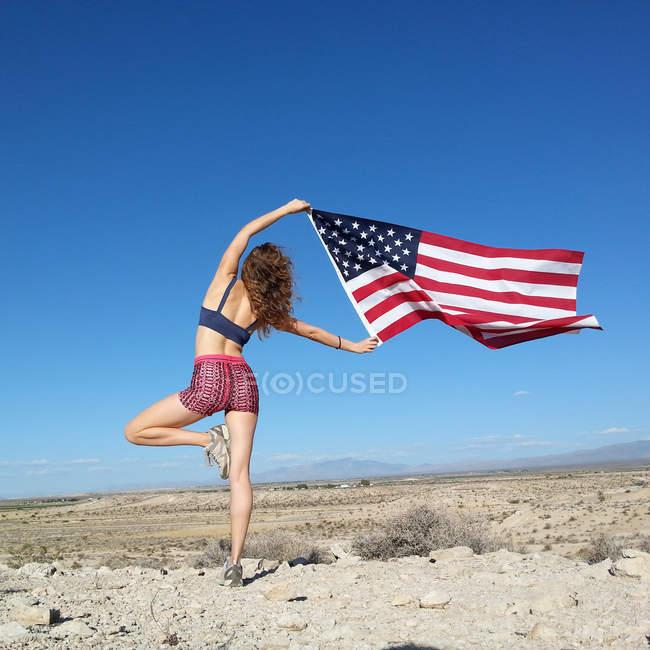 Жінки роблять поза дерева в пустелі і тримає американський прапор, Невада, Америка, США — стокове фото