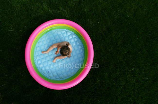 Vue aérienne d'une petite fille assise dans un gonflable multicolor remplissage piscine — Photo de stock