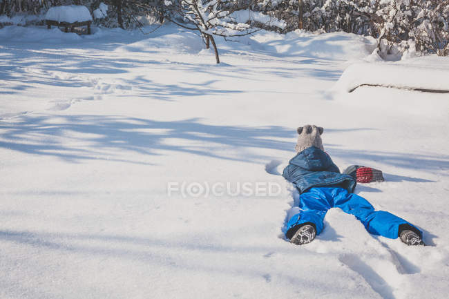 Girl lying on front in snow in winter forest — Stock Photo