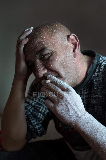 Hombre cubierto de pintura fumar cigarrillo - foto de stock