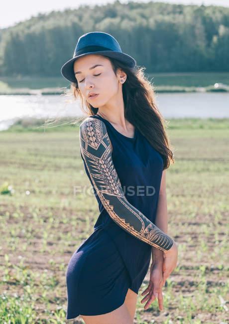 Женщина-хипстер с тату-рукавом стоит в сельской местности — стоковое фото