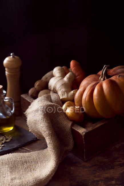 Kürbis, Ingwer, Olivenöl, Zwiebeln und Gewürze auf Holz — Stockfoto