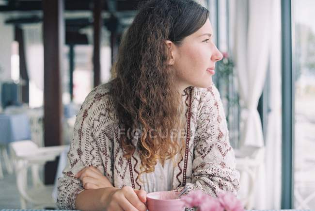 Woman enjoying a cup of coffee in cafe and looking through window — Stock Photo