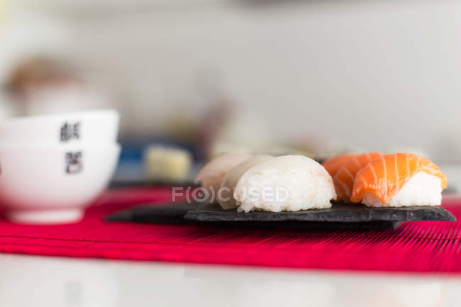 Tasty nigiri sushi and maki rolls against blurred background — Stock Photo