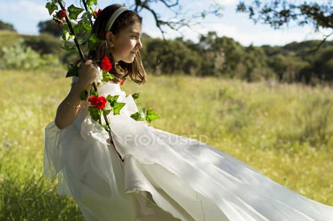 Дівчина першого причастя плаття, сидячи на гойдалки в галузі — стокове фото