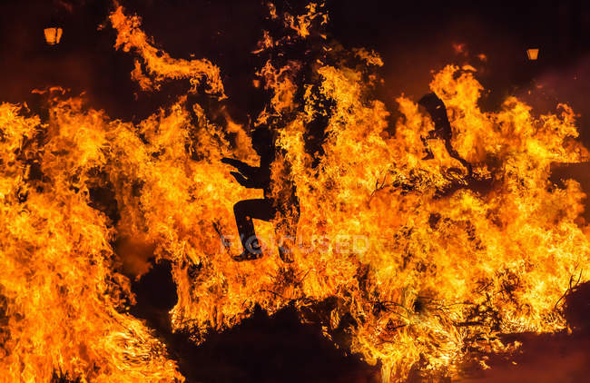 Silhouette of man running through fire at night — Stock Photo