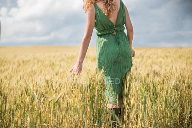 4cc15fbdc3f9 Vista posteriore della donna che indossa il vestito verde permanente nel  campo di frumento — Foto