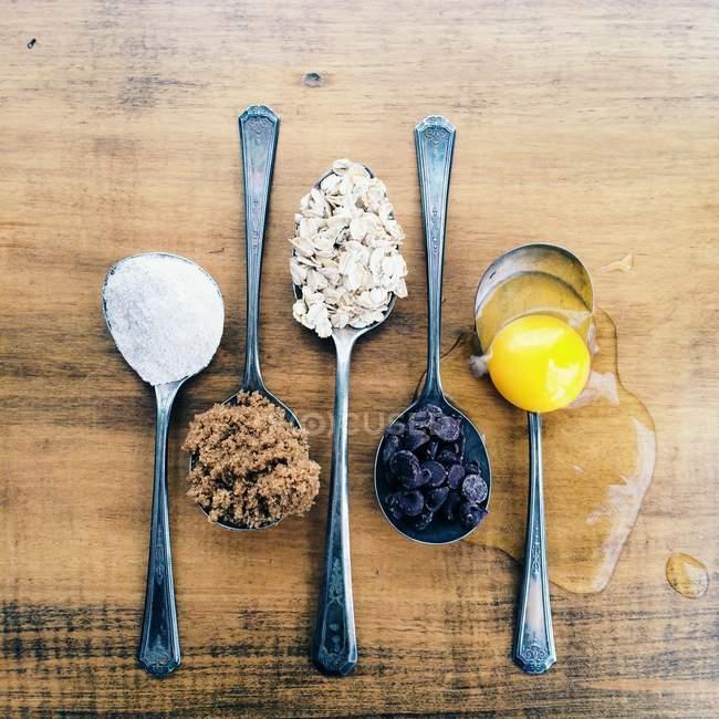 Ложки с куки ингредиенты над деревянными фоне — стоковое фото