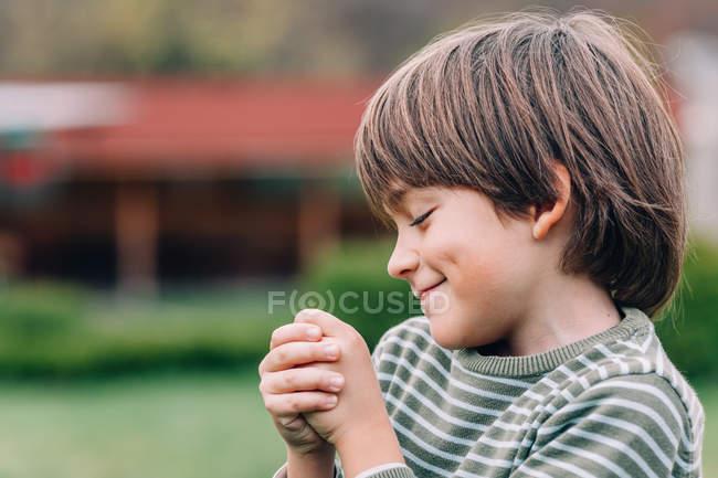 Ritratto di timido ragazzo sorridente con gli occhi chiusi — Foto stock
