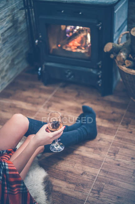 Cropped image of attractive woman with beautiful skin in sweater and socks sitting by fireplace at home and holding glass of wine — Stock Photo
