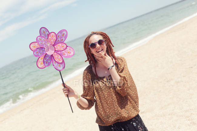 Smiling woman with dreadlocks standing on beach and holding plastic peacock windmill toy — Stock Photo
