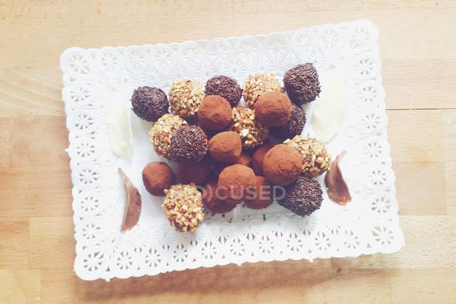 Plate of mixed chocolate truffles over wooden table — Stock Photo