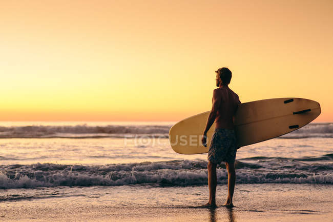 Man standing on beach at sunrise holding surfboard — Stock Photo