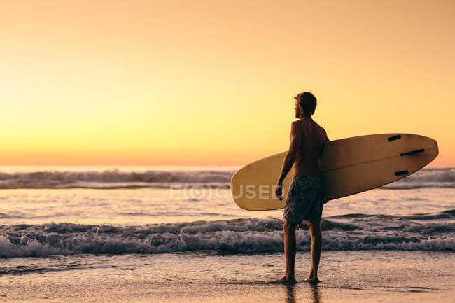 Man standing on beach at sunrise holding surfboard — Stock Photo